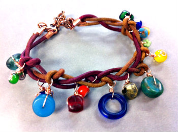 bracelet made from braided leather with charms hanging from it made of antique glass beads, gemstones, and brass findings