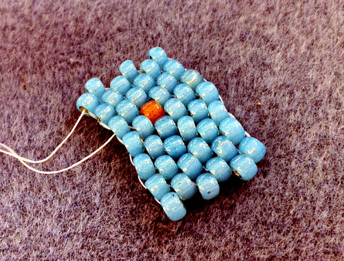 turquoise blue peyote stitch piece with an orange bead randomly stitched in; aka a 'spirit bead.'