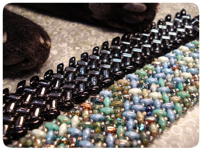two bracelets, same pattern with different beads used. The left one is hematite rullas and black seed beads and long magatamas, and the right one is an earthy blue mix of superduos and a pale, silvery seed bead.