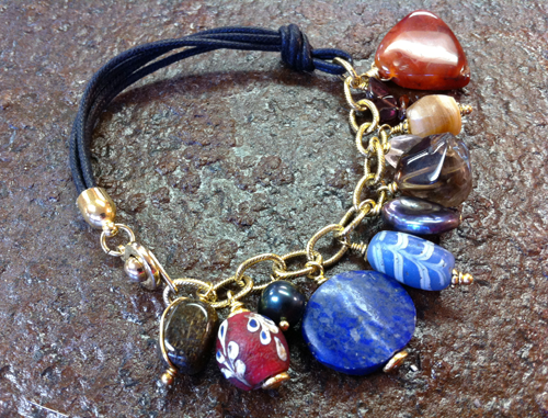 bracelet made out of chain and leather with large charms hanging from the chain. The charms are made from antique trade beads and gemstones