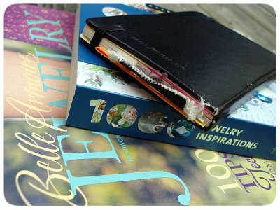 A stack of books: one magazine, one bead book, and a journal thick with added papers.