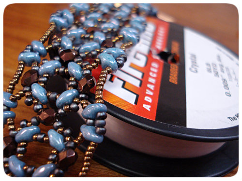a beadwoven bracelet made from blue Super Duos and antique bronze colored seed beads and Czech fire polish alongside a spool of Fireline thread.